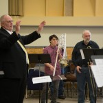 Mark Lusk conducting the choir. Kim Scharnberg, composer, in background.